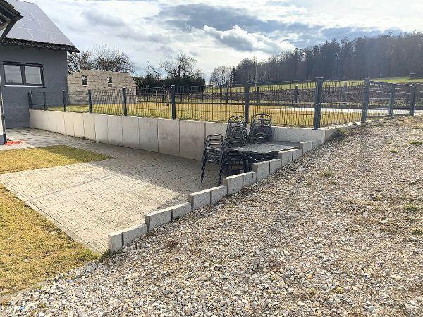 Fertige Winkelstützmauer mit Doppelstabmattenzaun als Absturzsicherung und Freisitz auf abgesenktem Niveau