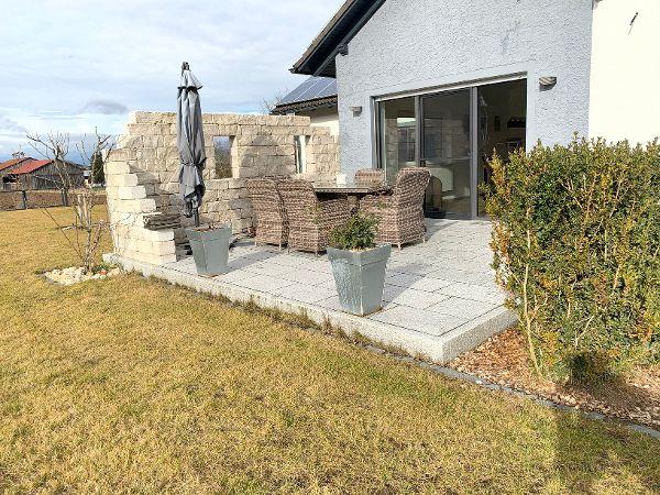 Fertige Terrasse mit Sichtschutz aus Natursteinmauerwerk und Plattenbelag aus Granit