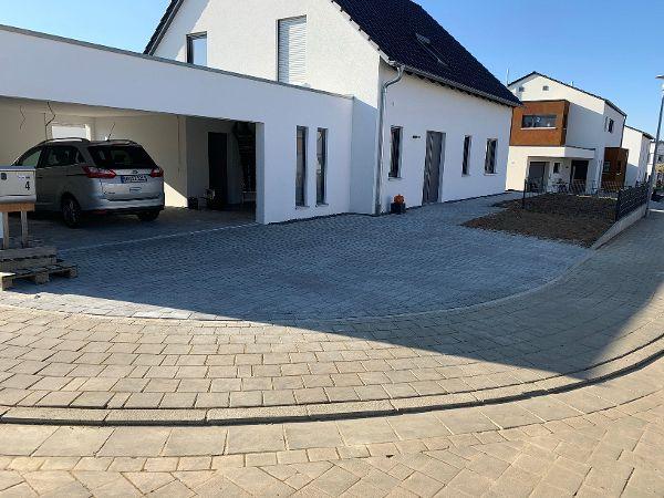 Fertig gepflasterte Hofeinfahrt mit grauen Pflastersteinen 16×24×8cm