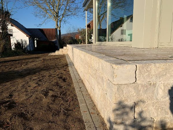 Mauersteine aus Jura-Kalkstein stützen die Terrasse und grenzen Sie zum Garten hin ab