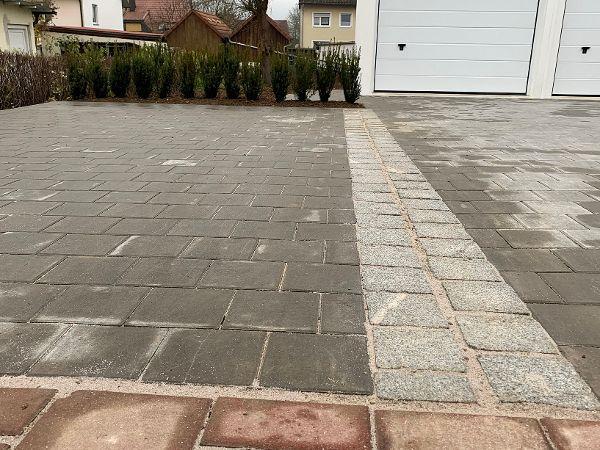 Zweizeiler aus Granit als Abgrenzung zum Parkplatz