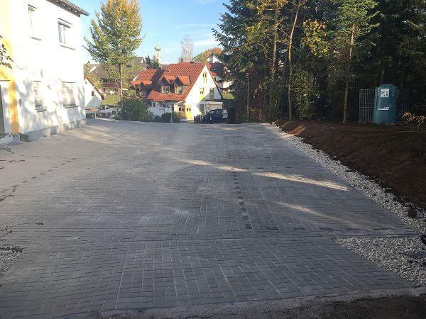 Fertige Parkplatzfläche, gepflastert mit grauen Complex-Pflastersteinen