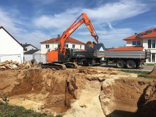 Aushub der Baugrube; das Aushubmaterial wird auf den Lkw verladen.