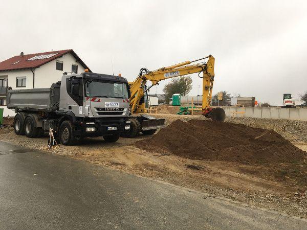 Verladen des felsigen Rohrgrabenaushubs und Abfuhr per Lkw