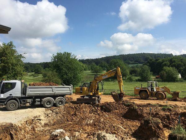 Baugrubenaushub und Verladen des Aushubs auf den Lkw. Der Aushub wird zur Deponie Waldhausen abgefahren.