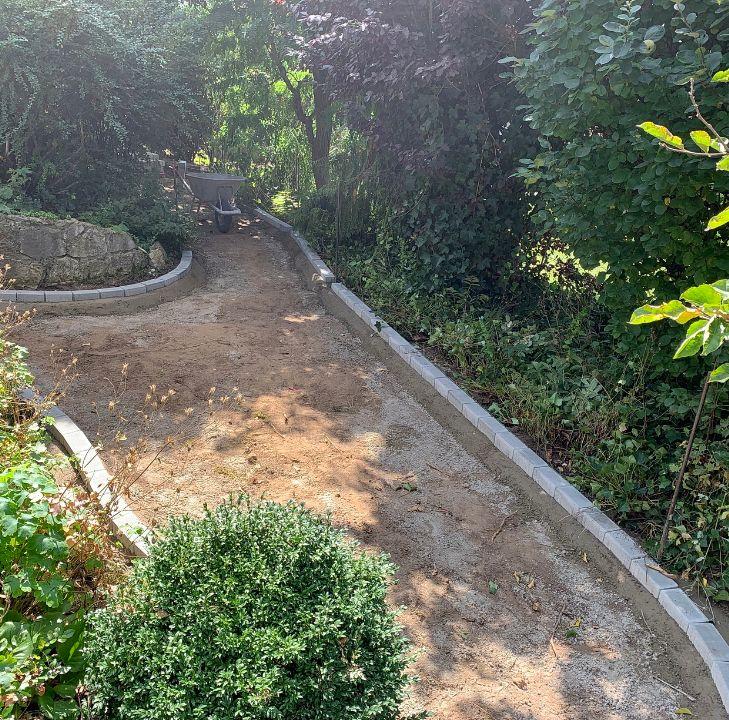 Gartenneugestaltung mit Natursteinmauer und Natursteinplatten